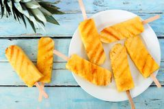 Plate of grilled pineapple wedges against rustic blue wood Royalty Free Stock Photos