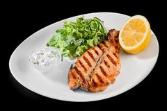 Plate with grilled salmon with lemon and greens on a black background. Royalty Free Stock Photos