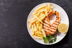 Plate of grilled salmon steak with french fries, top view royalty free stock photos