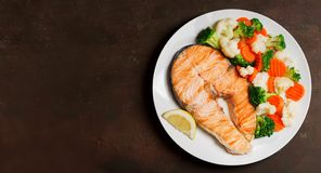 Plate of grilled salmon steak with vegetables, top view. Plate of grilled salmon steak with vegetables on old table, top view royalty free stock photo