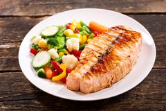 Plate of grilled salmon steak with vegetables stock photos