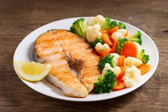 Plate of grilled salmon steak with vegetables. On wooden table royalty free stock photos