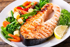 Plate of grilled salmon steak with vegetables stock images