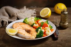 Plate of grilled salmon steak with vegetables. On wooden table stock photo