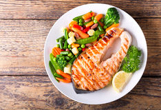 Plate of grilled salmon steak with vegetables. On wooden table, top view royalty free stock images