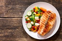 Plate of grilled salmon steak with vegetables royalty free stock photos