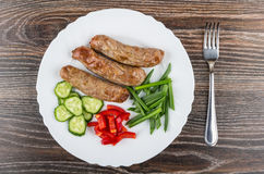 Plate with grilled sausages, cucumber, sweet pepper, scallion an. White plate with grilled sausages, pieces of cucumber, sweet pepper, scallion and fork on Royalty Free Stock Images