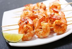 Plate of grilled shrimps with lime stock image