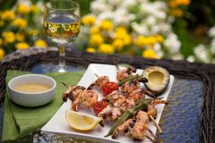 Grilled Shrimps Skewers for Dinner in Garden. Plate of grilled shrimps skewers with grilled vegetables and avocado. Served with lemon and lemon butter sauce Royalty Free Stock Image