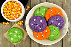 Plate of Halloween monster eyeball cookies with candy corn. Colorful Halloween monster eyeball cookies on a plate against rustic wooden background with candy Royalty Free Stock Photography