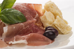 Plate of ham with cheese decorated close up. Plate of ham with cheese decorated! Basil, olive and parma ham closeup Stock Photos