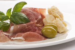 Plate of ham with cheese decorated close up 3. Plate of ham with cheese decorated! Basil, olive and parma ham closeup 3 Stock Image