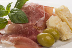 Plate of ham with cheese decorated close up 4. Plate of ham with cheese decorated! Basil, olive and parma ham closeup 4 Stock Photo