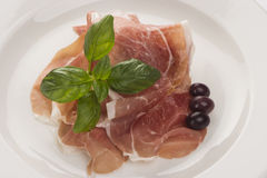Plate of ham with cheese decorated from the top. Plate of ham with cheese decorated! Basil, olive and parma ham from the top Stock Image