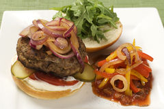 Plate with hamburger and salsa pepper salad Royalty Free Stock Image