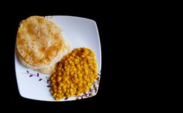 Plate having luchi and cholar dal gram gravy on a plate in black backgroundwith space for text stock photography