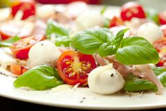 Plate of healthy classic delicious caprese salad with ripe tomatoes and mozzarella cheese with fresh basil leaves on white wooden royalty free stock photo