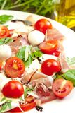 Plate of healthy classic delicious caprese salad with ripe tomatoes and mozzarella cheese with fresh basil leaves on white wooden stock photography