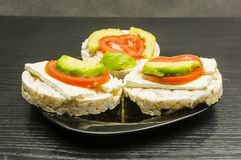 Healthy and dietary sandwiches - rice cake with cheese, tomato a. Plate with healthy and dietary sandwiches - rice cake with cheese, tomato and avocado stock image
