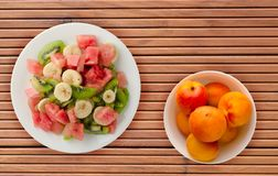 Plate of healthy fresh fruit salad on wooden background.  stock photos