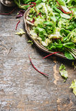 Plate with healthy green salad on wooden background. Royalty Free Stock Photography