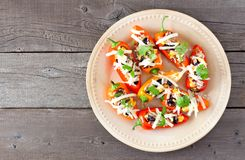 Plate of healthy stuffed mini peppers against wood Royalty Free Stock Photography