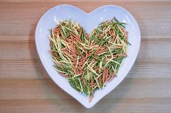 Plate-heart, pasta, space for text. Multicolored pasta in a wooden plate. I love macaroni royalty free stock photography