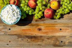 Plate of homemade cottage cheese, grapes and peach on wooden rustic table. stock photos