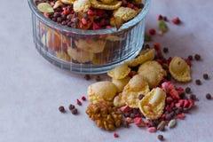 Plate of homemade muesli with cornflakes, freeze dried strawberry, walnuts, chocolate balls, pumpkin seeds Stock Photo