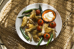 Plate of hot delicious wings on straw background Royalty Free Stock Images