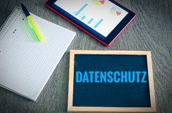 Plate with the inscription in german Datenschutz in English data protection with a tablet and block to signal typical activities royalty free stock photography