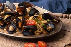 Plate with italian pasta and mussels in shells, tomatoes and rosemary on wooden background stock images