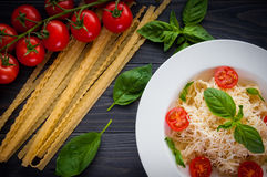 Plate of italian pasta with tomatoes, basil and cheese. On a dark wooden backgrounde close up Stock Photo