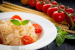 Plate of italian pasta with tomatoes, basil and cheese. On a dark wooden backgrounde close up Stock Photos