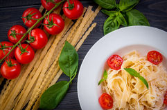 Plate of italian pasta with tomatoes, basil and cheese. On a dark wooden backgrounde close up Royalty Free Stock Photography