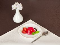 Plate with jelly, spoon and flowers in vase Stock Photo
