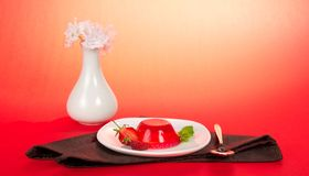 Plate jelly, spoon, vase with the flowers Royalty Free Stock Image