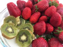 A plate with juicy ripe berries strawberries and kiwi. Fruit photography. in a transparent plate lies a fresh, large, red strawberry and sliced kiwi slices Royalty Free Stock Images