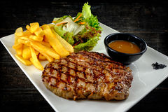 Plate with juicy stake, french fries and salad. stock photography