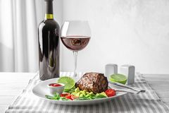 Plate with juicy steak and glass of wine on table. Against light background Stock Photo