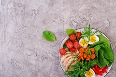 Cherry tomatoes, chicken breast, eggs, carrot, salad with arugula royalty free stock photo