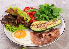 Plate with a keto diet food. Fried egg, bacon, avocado, arugula and strawberries. stock photo