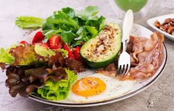 Plate with a keto diet food. Fried egg, bacon, avocado, arugula and strawberries. royalty free stock images