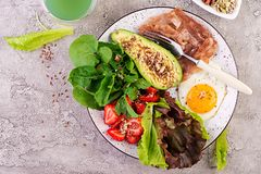 Plate with a keto diet food. Fried egg, bacon, avocado, arugula and strawberries. stock photography