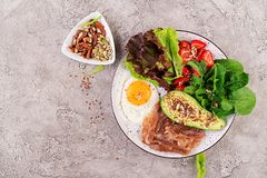 Plate with a keto diet food. Fried egg, bacon, avocado, arugula and strawberries. stock images