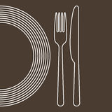 Plate, knife and fork. On a brown background Stock Photo