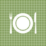 Plate knife and fork on green tablecloth Royalty Free Stock Images