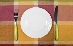 Plate with knife and fork on the table Royalty Free Stock Photo