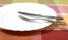 Plate with knife and fork on the table Stock Photos