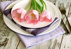 Plate, knife, fork and tulips on wooden Stock Photo
